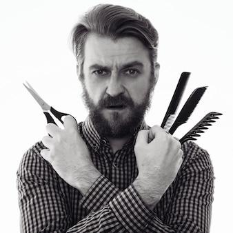Cabeleireiro barbudo sério segurando uma tesoura e um pente