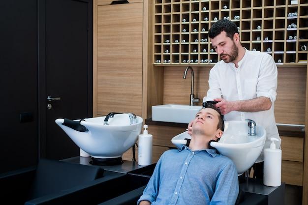 Cabeleireiro cabeleireiro lavar o cabelo do cliente - jovem relaxante no salão de beleza de cabeleireiro