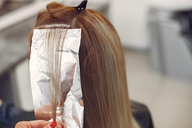 Cabeleireiro cabelo colorido seu cliente em um salão de cabeleireiro