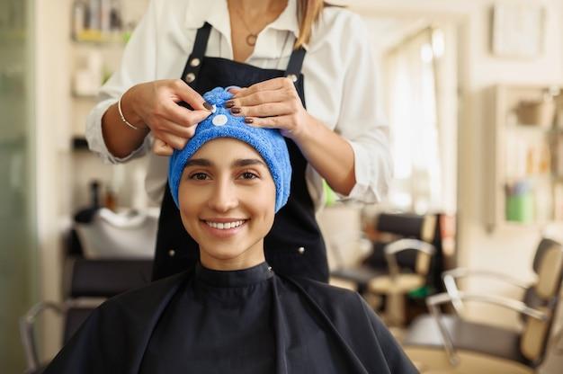 Cabeleireiro coloca toalha no cabelo da mulher, vista frontal, salão de cabeleireiro. estilista e cliente em hairsalon. negócio de beleza, serviço profissional