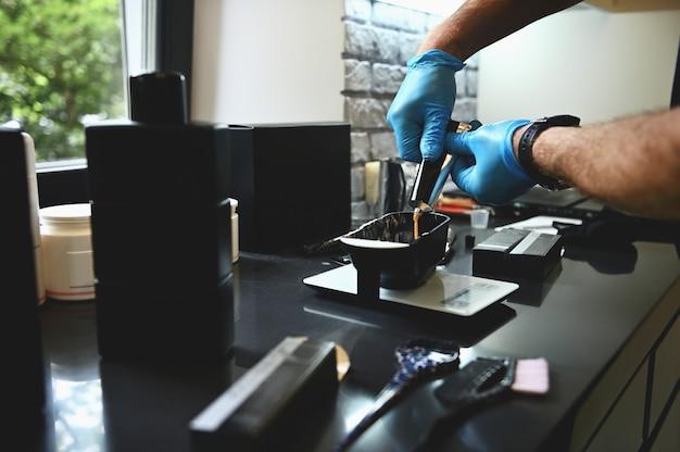 Cabeleireiro com as mãos em luvas de borracha, derramando um pigmento de cor líquida de um tubo em uma tigela.