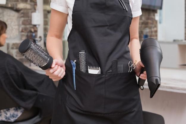 Cabeleireiro com escova e secador de cabelo