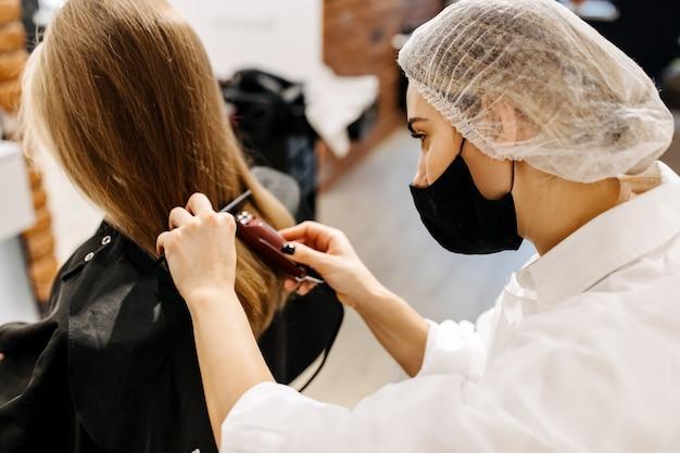 Cabeleireiro com máscara, cortando o cabelo de clientes com uma tesoura de cabelo, em um salão de beleza