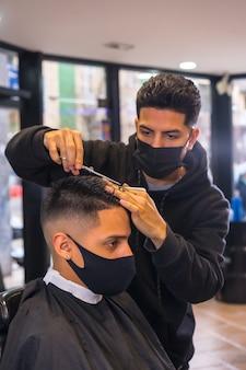Cabeleireiro com máscara de corte de cabelo. medidas de segurança no novo normal de cabeleireiros na pandemia de covid-19