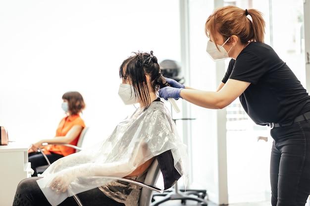 Cabeleireiro com máscara e luvas trabalhando com um cliente. reabertura com medidas de segurança de cabeleireiros na pandemia de covid-19