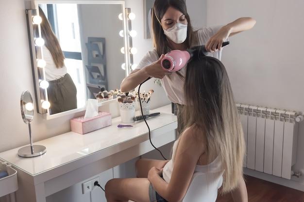 Cabeleireiro com máscara penteando e alisando os cabelos da cliente. sessão de cabeleireiro em tempos de pandemia.