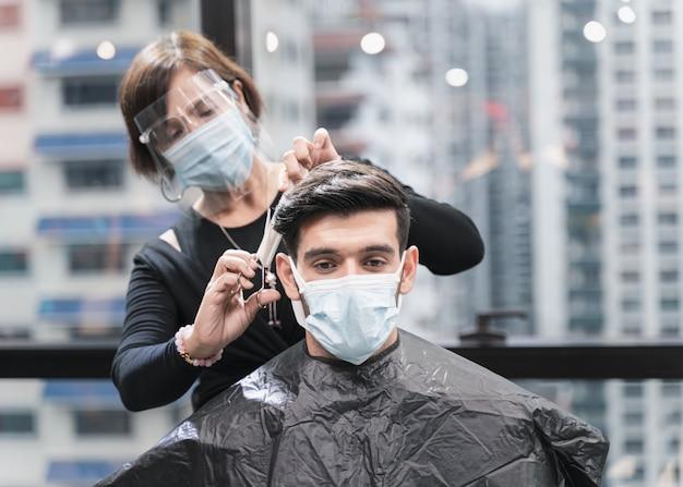 Cabeleireiro com medidas de segurança para covid-19 ou coronavírus, cabelo cortado por um homem em uma máscara de medicamento