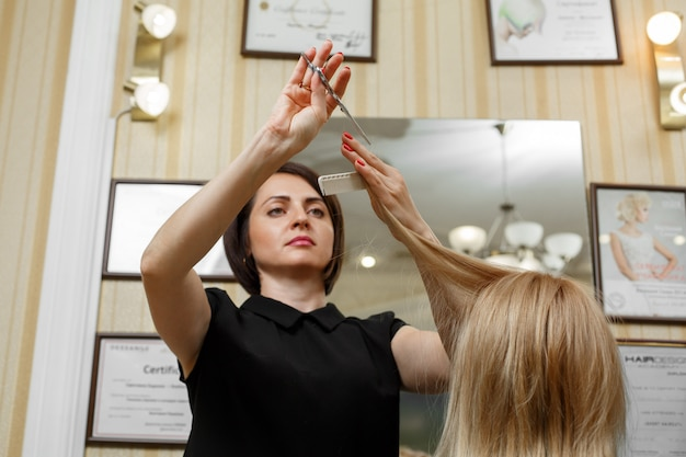 Cabeleireiro com tesoura e pente nas mãos fechar. cabeleireiro cortará as pontas dos cabelos loiros bem arrumados. mestre de cabelos.