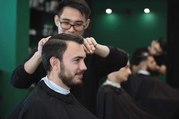 Cabeleireiro com um pente e uma tesoura corta um homem barbudo em uma poltrona em uma barbearia