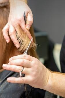 Cabeleireiro corta cabelo castanho de jovem em salão de beleza
