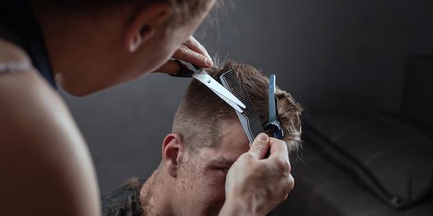 Cabeleireiro corta o cabelo com uma tesoura em fundo cinza, barbearia.