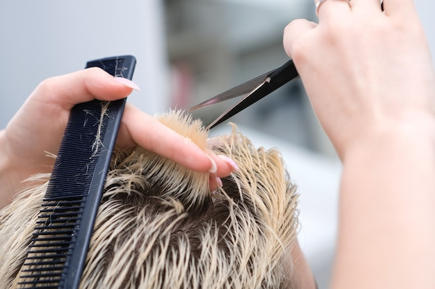 Cabeleireiro corta o cabelo de um jovem com cabelos tingidos de loiro com uma tesoura em um salão de beleza. cuidado profissional do cabelo.