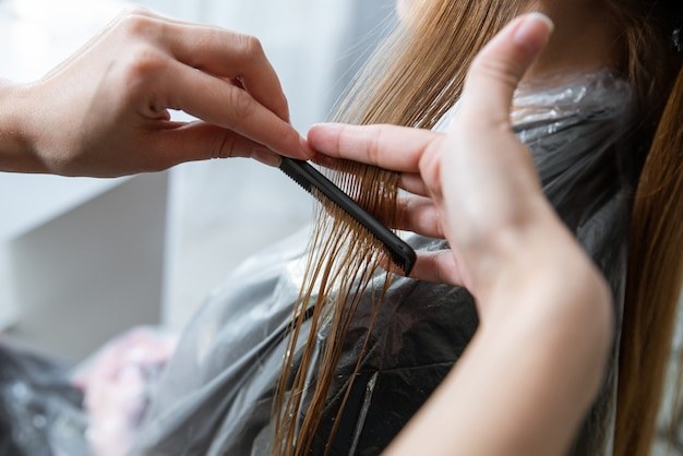 Cabeleireiro corta o cabelo de uma jovem loira no salão de cabeleireiro