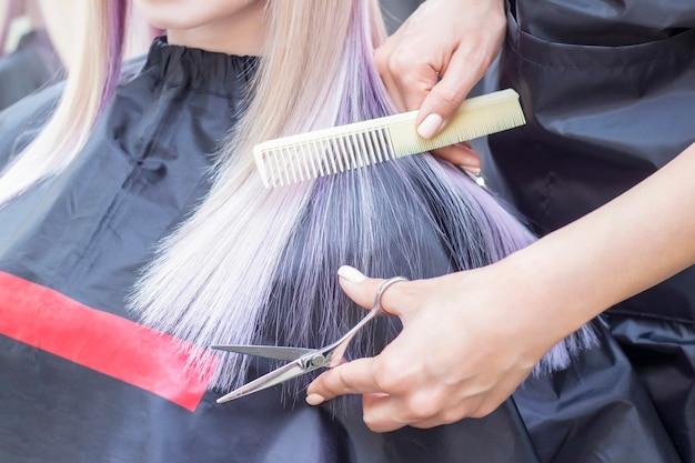 Cabeleireiro corta o cabelo de uma menina com longos cabelos loiros