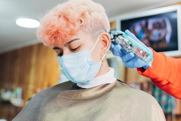 Cabeleireiro cortando cabelo para mulher usando máscara facial em uma barbearia. novo normal após covid.