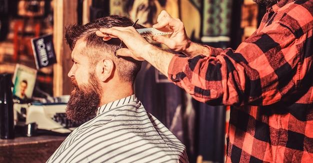 Cabeleireiro cortando o cabelo de um cliente do sexo masculino. homem visitando cabeleireiro na barbearia. tesouras de barbeiro. homem barbudo na barbearia. trabalho na barbearia. cabeleireiro de homem.