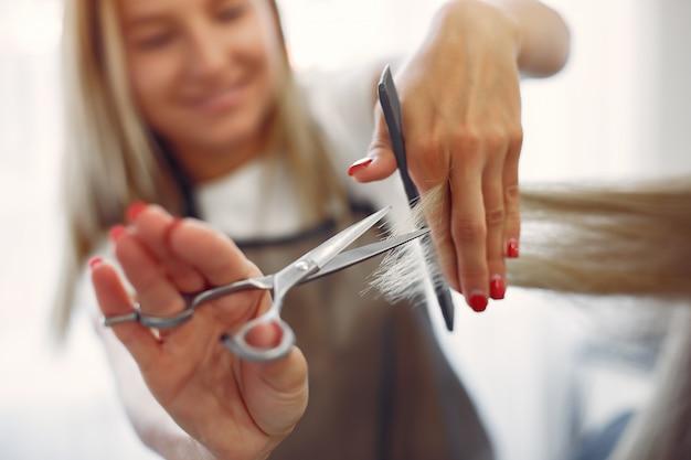 Cabeleireiro cortar o cabelo de seu cliente em um salão de cabeleireiro