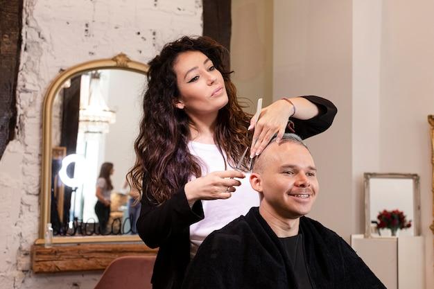 Cabeleireiro cortar o cabelo do homem no salão de beleza