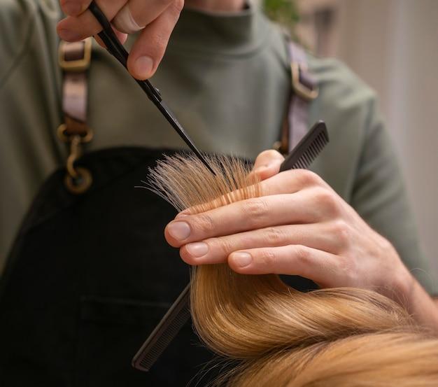 Cabeleireiro cuidando do cabelo de uma cliente dentro de casa