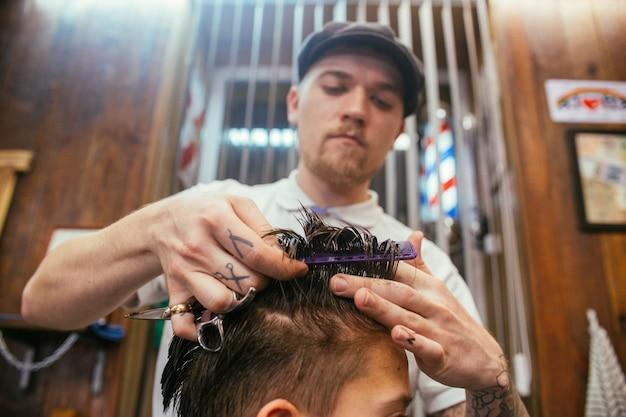 Cabeleireiro de cabeleireiro de adolescente em barbearia