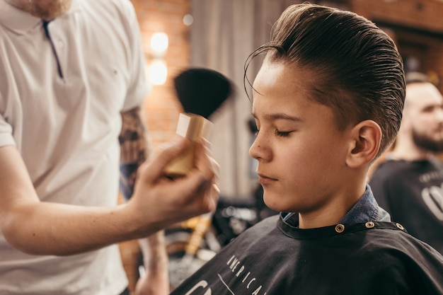 Cabeleireiro de cortes de cabelo de adolescente na barbearia
