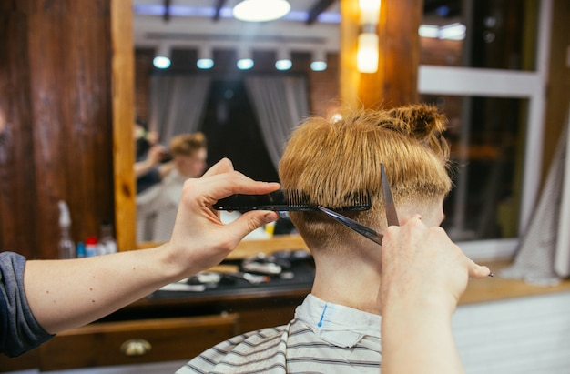 Cabeleireiro de cortes de cabelo de menino ruivo adolescente na barbearia. elegante