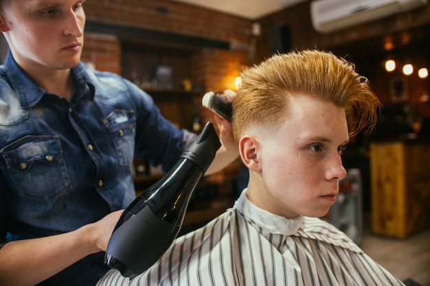 Cabeleireiro de cortes de cabelo de menino ruivo adolescente na barbearia. penteado retrô elegante na moda