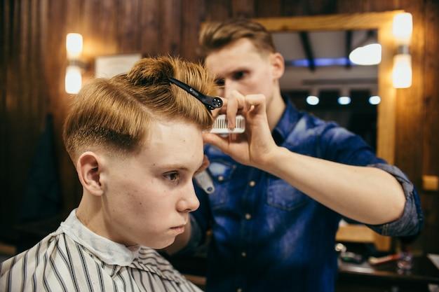 Cabeleireiro de cortes de cabelo de menino ruivo adolescente na barbearia