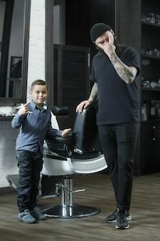 Cabeleireiro de crianças cortando o garotinho contra um fundo escuro.