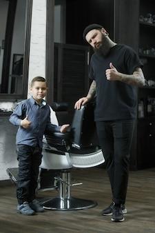 Cabeleireiro de crianças e menino contra um fundo escuro, após o corte de cabelo. a mão do mestre tem tatuagem com a palavra barbear