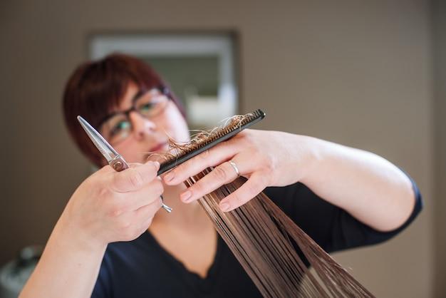 Cabeleireiro de estilista fazendo o corte de cabelo closeup de equipamentos de trabalho