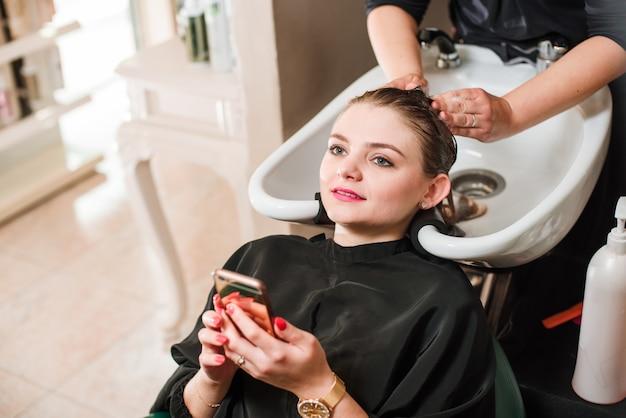 Cabeleireiro e mulher durante a lavagem do cabelo