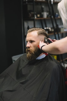 Cabeleireiro elegante corte de cabelo de cliente na barbearia.