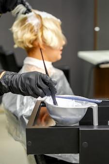 Cabeleireiro em luvas pretas tingindo o cabelo de uma jovem em um salão de cabeleireiro