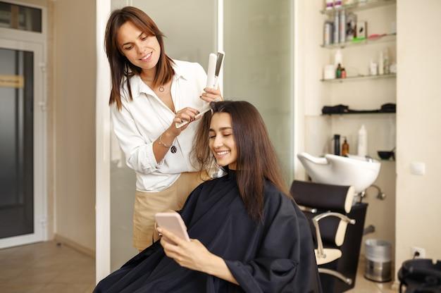 Cabeleireiro endireita o cabelo da mulher, salão de cabeleireiro. estilista e cliente em hairsalon. negócio de beleza, serviço profissional