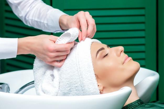 Cabeleireiro envolvendo o cabelo da mulher na toalha após lavar a cabeça no salão de beleza, close-up.