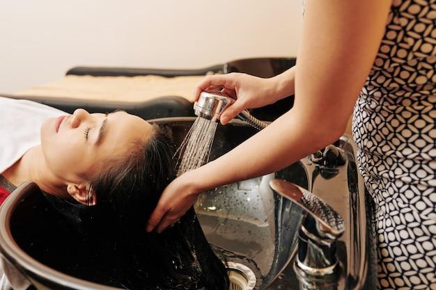 Cabeleireiro enxaguar o cabelo dos clientes
