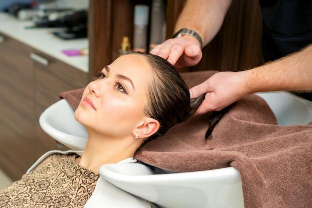 Cabeleireiro enxuga o cabelo com a toalha da jovem após a lavagem no salão de cabeleireiro