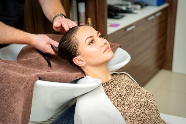 Cabeleireiro enxuga o cabelo com uma toalha de mulher jovem após a lavagem no salão de cabeleireiro