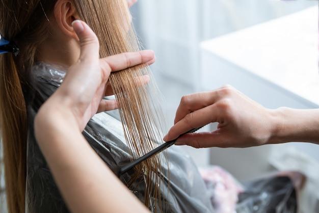 Cabeleireiro, escovar os longos cabelos loiros com escova no salão de beleza