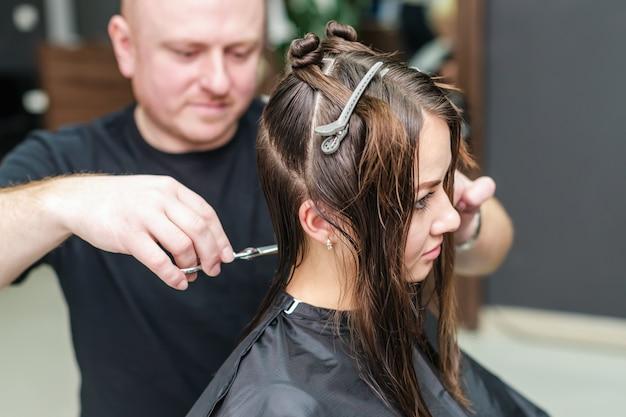 Cabeleireiro está cortando o cabelo de mulher em salão de beleza.