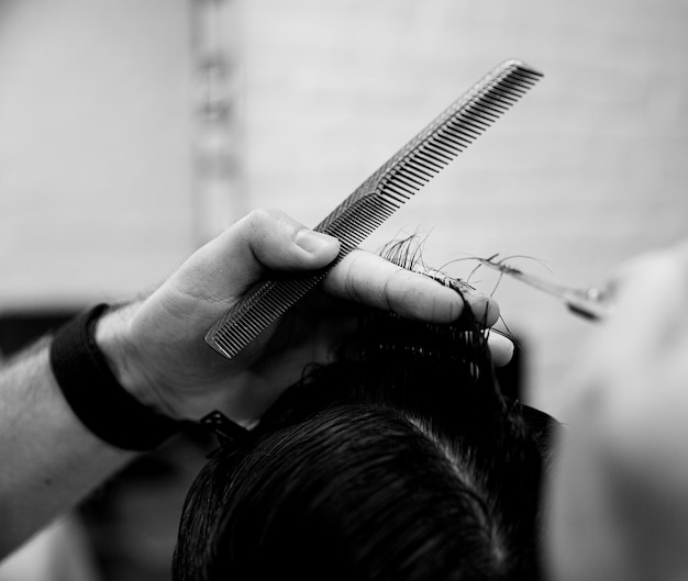 Cabeleireiro está cortando o cabelo do cliente