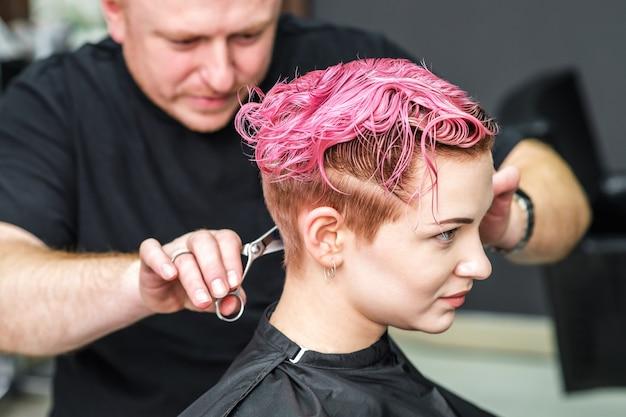 Cabeleireiro está cortando o cabelo rosa de uma mulher.