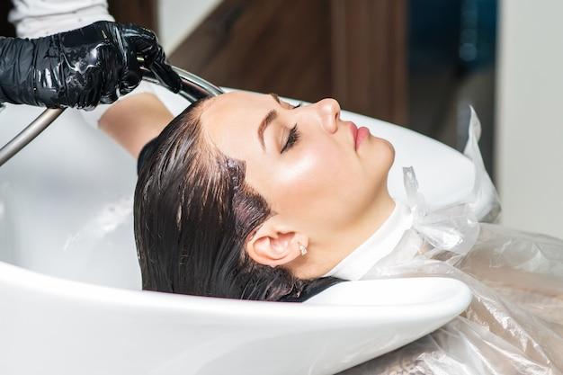 Cabeleireiro está lavando o cabelo de jovem no salão de beleza.