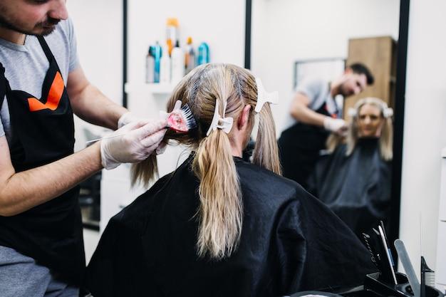 Cabeleireiro está morrendo de raízes de cabelo de mulher madura.