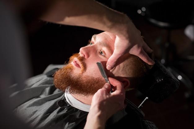 Cabeleireiro está raspando a barba masculina com a faca. bonito homem barbudo está sendo barbeado por cabeleireiro na barbearia
