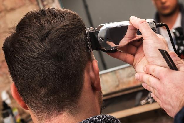 Cabeleireiro está trabalhando com uma máquina de cortar cabelo