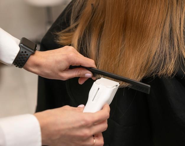 Cabeleireiro estilizando o cabelo de uma cliente no salão