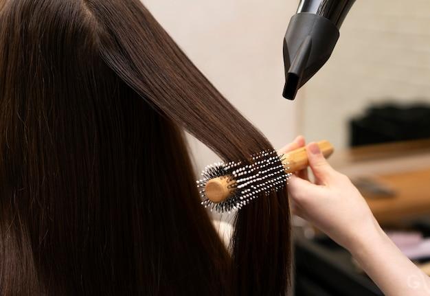 Cabeleireiro estilizando o cabelo de uma cliente
