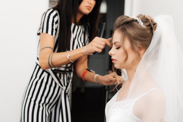 Cabeleireiro faz estilismo para uma linda noiva em um salão de beleza profissional